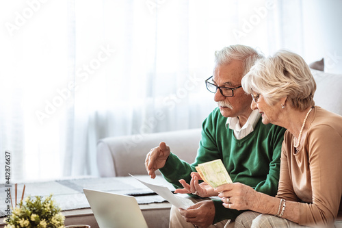 Fototapeta Serious senior husband and wife doing their home financials in the living room