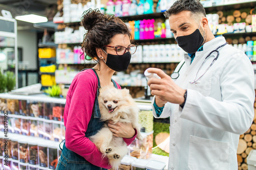 Fototapeta Female customer with protective face mask talking with veterinarian in pet shop and holding cute Pomeranian dog. obraz