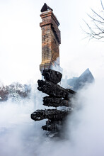 Remains Of A House After A Fire. The Brick Chimney Of The Stove And The Charred Planks Are Shrouded In Dense Smoke