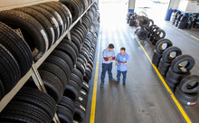 Two Mechanics Working The Tire Area Of An Auto Repair Shop, Using A Digital Tablet