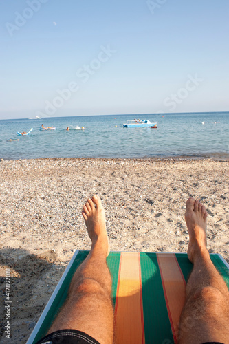 Tablou Canvas Man lying down on a sunbed at the beach