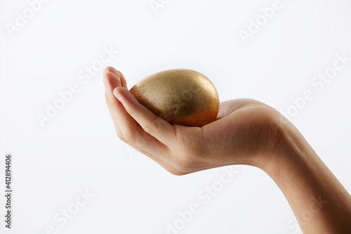 Fotografie, Obraz Cropped Hand Of Woman Holding Gold Egg Against White Background