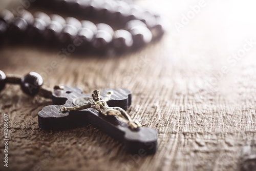 Tela wooden rosary radiated by divine light, concept of faith and spirituality, copy