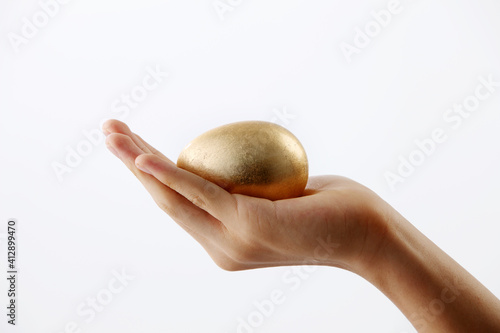 Fototapeta Cropped Hand Of Woman Holding Gold Egg Against White Background