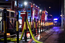 Fire Brigade In Action. Close Up Of Yellow Fire Hose With Fire Truck Lights In Background. Firefighters In Action. Many Fire Trucks And Police Car In Background.