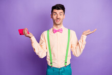 Photo Of Uncertain Young Man Raise Hands Clueless Hold Smartphone Wear Green Suspenders Isolated On Violet Color Background