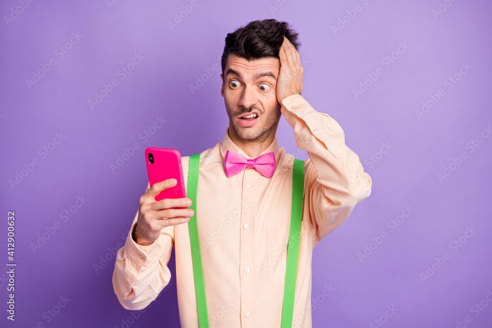 Fototapeta Photo of shocked astonished brunette man hold hand head look read fake news phone isolated on purple color background