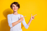 Photo portrait of woman pointing two fingers at blank space isolated on bright yellow colored background