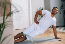 Cheerful Sporty African-American Man Exercising In Side Plank Position On Floor During Working Out At Bright Domestic Room. Concept Of Sport Training At Home Gym.