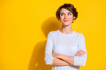 Photo of shiny sweet young lady dressed white shirt arms crossed looking empty space isolated yellow color background