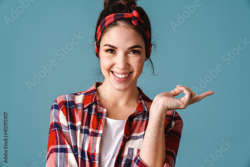 Fotografija Joyful caucasian young woman smiling and pointing finger aside