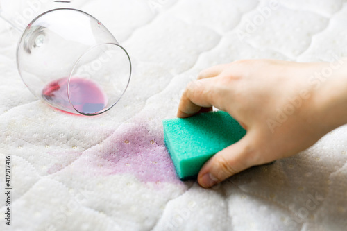 Close-up Of Hand Cleaning Wine Stain On Mattress At Home © mikhail pivikov/EyeEm