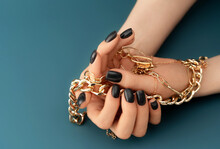 Female Hands With Trendy Dark Nail Design With Gold Bracelets On Aqua Background. Luxury Concept. Festive Backdrop For Your Design.
