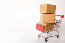 Close-up Of Boxes Stack In Shopping Cart Over White Background