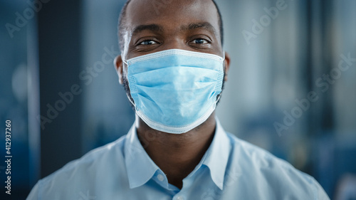 Close Up Portrait of a Black African American Handsome Male in White Shirt Wearing a Protective Face Mask. Successful Man Calmly Looking at Camera. Stylish Businessman or a Doctor in Hospital.