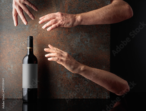 Hands reach for a bottle of red wine. © Igor Normann