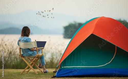 Tela A sense of peace and serenity photo of female traveler sitting beside camping te