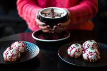 Traditional French Dessert - Eclairs Or Profiteroles With White Halloween Eyes Created From Icing. A Woman In A Pink Sweater Is Holding A Coffee Cup With A Cobweb. Halloween Concept