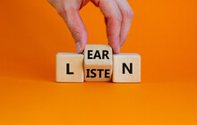Listen And Learn Symbol. Businessman Turns A Wooden Cube And Changes The Word 'listen' To 'learn'. Beautiful Orange Background, Copy Space. Business, Education And Listen And Learn Concept.