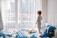 Cute Little Boy Toddler Standing On Bed In Room And Looking Into Window Waiting Expecting Someone. Child Staring Watching From Home Outside Into Street. A Lonely Kid Playing Alone At Home.