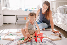 Mother And Toddler Boy Playing With Car Wooden Railway On Floor At Home. Early Age Education Development. Kids Building Rail Road And Playing Educational Toy Trains Cars. Leisure Activity For Kids.