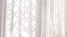 White Voile Or Net Curtain Hung At Criss Cross Design Window