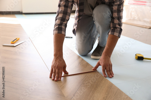 Obraz Worker installing laminated wooden floor indoors, closeup - fototapety do salonu