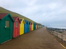 Multi Colored Beach Huts By Sea Against Sky