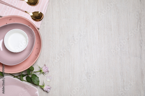 Fototapeta Flat lay composition with beautiful dishware and roses on white wooden table. Space for text obraz