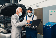 Car Mechanic Talking With Senior Business Man Costumer And  Looking At Laptop During Periodic Car Condition Check. They Are Wearing Protective Face Mask Against Virus Pandemic.