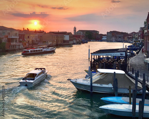 Fototapeta Boats Moored In Canal By Buildings Against Sky During Sunset