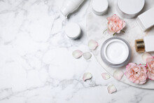 Flat Lay Composition With Different Skin Care Products And Flowers On White Marble Background, Space For Text