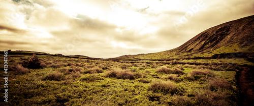 Artistic shot of bright clouds over a hill in a field - fototapety na wymiar