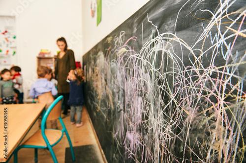 Art classroom in kindergarten, young teacher drawing with children on chalk wall Fotobehang