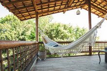 Modern Luxury Summer Holiday Or Vacation Wooden Beach House Balcony With A Hammock And Rustic Decoration With A Green Nature View.