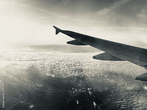 Fotografiet Cropped Image Airplane Wing Flying Over Sea Against Sky