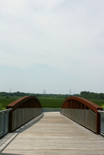 An Empty Walking Bridge At The Russell W. Peterson Urban Wildlife Refuge In The Riverfront Neighborhood Of Wilmington, Delaware