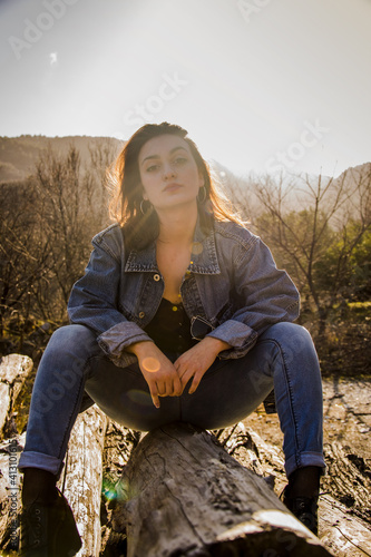 Canvas Print Portrait Of Young Woman Sitting On Rock Against Sky