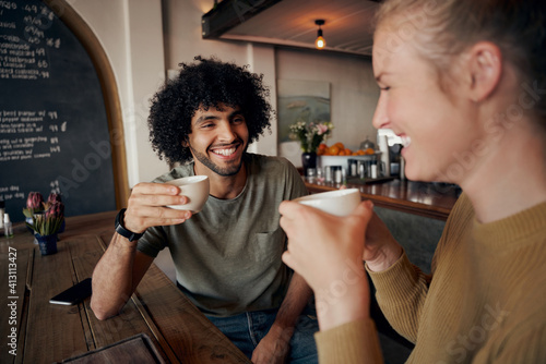 Obraz Cheerful young couple enjoying date while talking and laughing in modern cafe and drinking freshly brewed coffee - fototapety do salonu