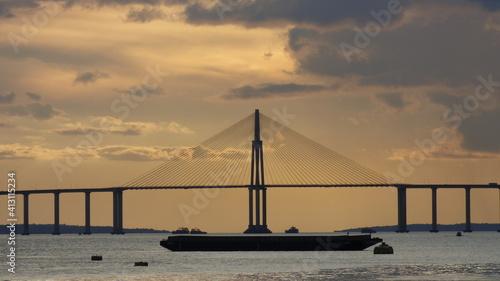 Fototapeta View Of Suspension Bridge Over Sea Against Cloudy Sky obraz
