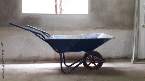 Fotografia Wheelbarrow By Window