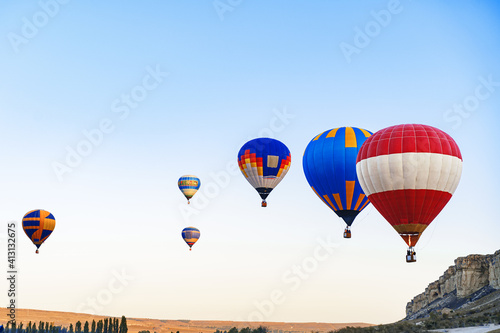 Foto Colorful air balloons flying in clear sky near huge white mountain