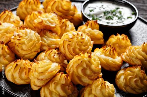 Fotografia Duchess potatoes served on a black plate