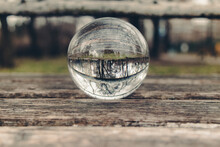 A Crystal Ball With Reflections Of White Rusty Iron And Trees In The Park