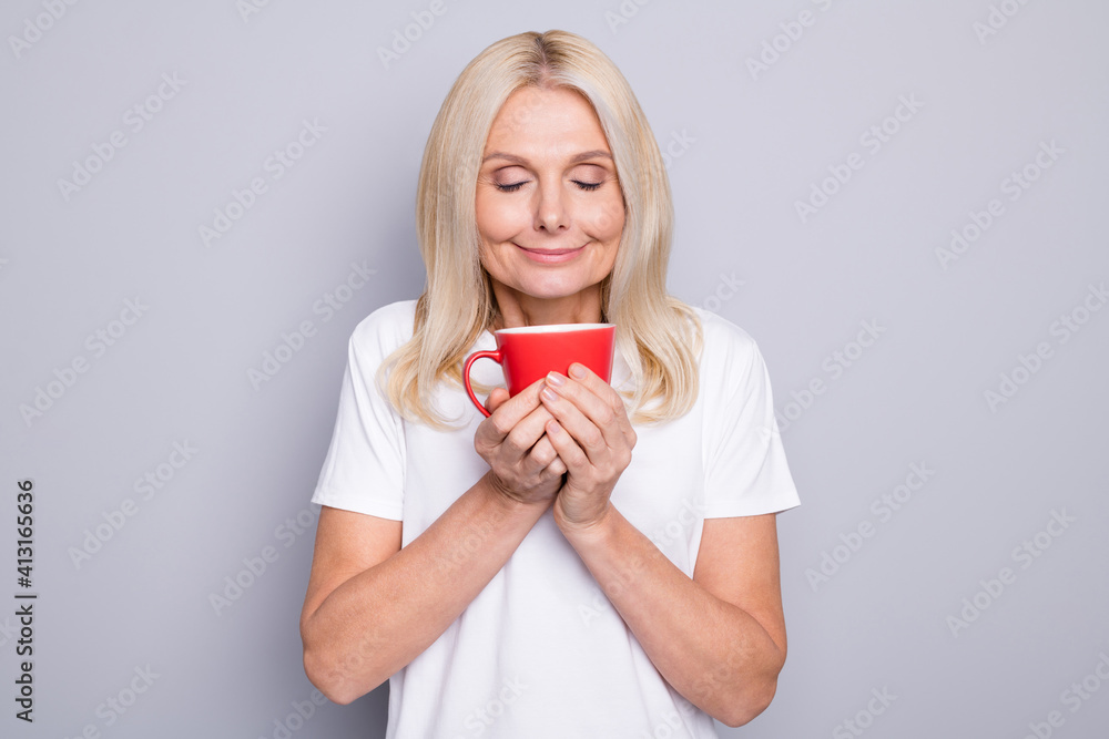 Fototapeta Photo portrait of old woman inhaling smell of nice morning coffee holding red cup in two hands isolated on grey colored background