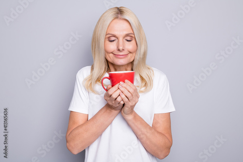 Fototapeta Photo portrait of old woman inhaling smell of nice morning coffee holding red cup in two hands isolated on grey colored background obraz