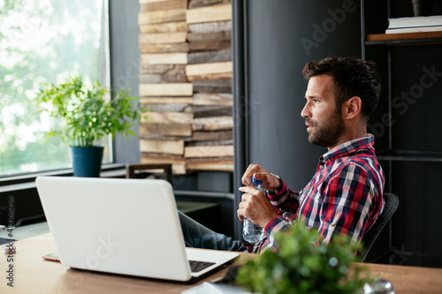 Fotografie, Obraz Young businessman using laptop in his office