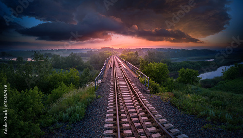Railway on the background of the evening stormy sky and sunset.