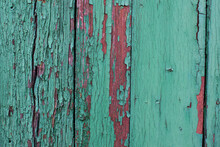Wood Texture With Green And Red Flaked Cracked Paint On Weathered Surface