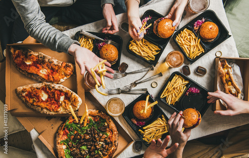 Obraz Lockdown fast food dinner from delivery service, getting together. Flat-lay of friends having quarantine party with burgers, french fries, sandwiches, pizza, beer over table background, top view - fototapety do salonu
